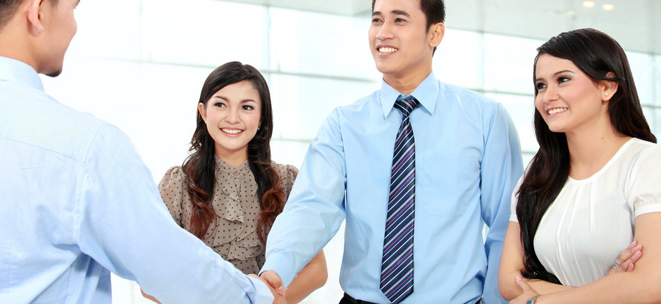 A business team with secretary in the office shaking hands